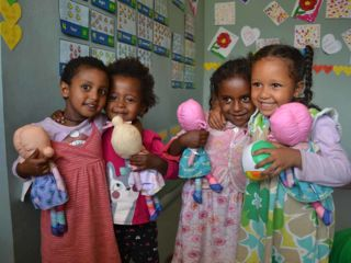 girls-holding-dolls-in-kindergarten-classroom.jpg