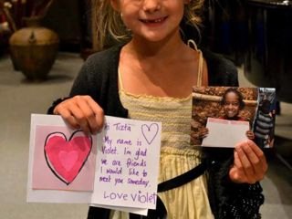 young-girl-holding-up-card-she-received-back.jpg