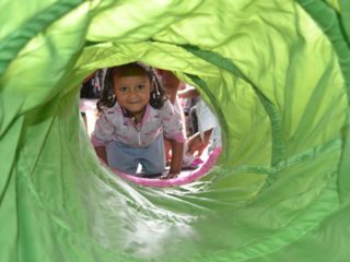 girl-playing-in-tunnel-at-daycare.jpg